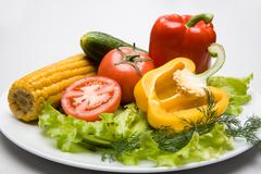 image of tomato, cucumber, pepper, maize and verdure placed on the plate - stock photo