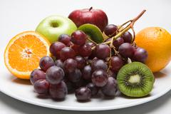 photo of kiwi, oranges, apples and bunch of vine placed on the plate - stock photo