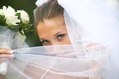 close-up of young green-eyed bride holding veil by her face and looking at camer - stock photo