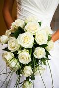 Close-up of white rose bouquet decorated with pearl beads in bride's hands Stock Photos