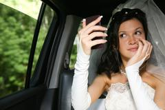 photo of happy woman in wedding dress looking at the mirror - stock photo