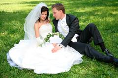 Portrait of happy couple sitting on the grass after marriage Stock Photos