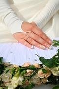 Photo of beautiful hands of bride over bunch of flowers Stock Photos