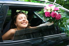 photo of happy bride with closed eyes holding rose bouquet in the car - stock photo