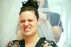 face of young woman expressing pain while her hair is being done for wedding - stock photo