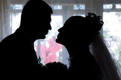 view of bride and groom silhouettes on the background of curtained window - stock photo