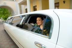 photo of young happy woman looking out of white limousine window with arc on the - stock photo