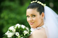 Portrait of pretty bride with white bouquet looking at camera Stock Photos