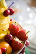 Close-up of juicy strawberries and cherries on plate with sliced pineapple near Stock Photos