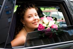 Photo of happy bride looking out of car window with bouquet in her hands Stock Photos