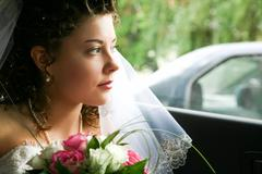 Face of bride looking from the car window with bunch of white and pink roses Stock Photos