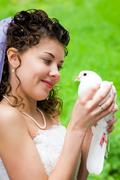 photo of beautiful bride holding white dove in hands and looking at it with smil - stock photo