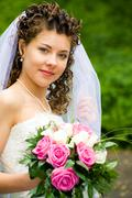 Portrait of beautiful bride with rose bouquet in hand looking at camera Stock Photos