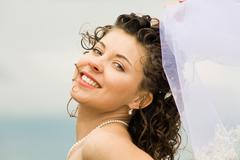Image of happy young bride touching wedding veil and looking at camera Stock Photos