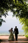 View of married couple holding hand of each other and walking to park Stock Photos