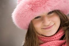 face of pretty woman wearing pink winter fur cap and looking at camera with smil - stock photo