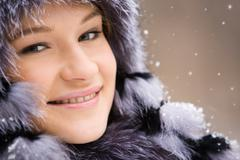 charming woman in fur clothing having walk out at winter during snowfall - stock photo