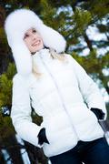 Portrait of charming female wearing winter clothing and having walk in forest Stock Photos