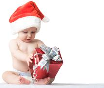 Photo of curious and surprised baby in santa cap looking at giftbox in his hands Stock Photos