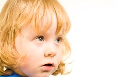 face of little redhead girl looking at something over white background - stock photo