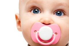 face of adorable baby with pacifier in mouth looking at camera - stock photo