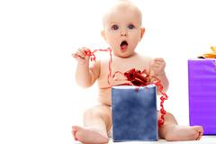 photo of surprised baby sitting with big giftbox by her side over white backgrou - stock photo