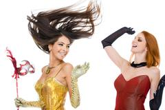 Photo of joyful actresses in fashionable dresses laughing over white background Stock Photos