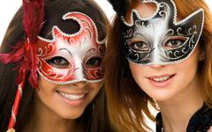 portrait of two smart ladies in masks at masquerade - stock photo