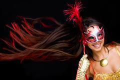 Portrait of pretty female looking through decorative mask on black background Stock Photos