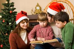 Little boy surrounded by his family members trying to read book Stock Photos