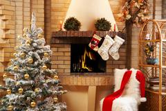 Christmas room with fireplace, chair, presents under decorated fir tree and toys Stock Photos