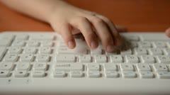 Child typing on a keyboard. Dolly shot - stock footage