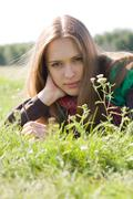 Portrait of attractive young female lying on green grass and looking at camera Stock Photos