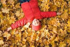 above view of peaceful child enjoying herself while lying on autumnal ground - stock photo