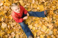above view of smiling girl sitting on autumnal ground and looking at camera - stock photo