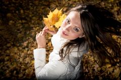 Above view of young girl holding dry leaves in autumn forest and looking at came Stock Photos