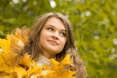 portrait of face of beautiful woman in autumnal environment - stock photo