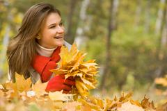 portrait of cheerful woman lying on autumnal land with maple leaves in hands - stock photo