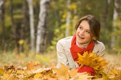 portrait of pretty young female holding dry leaves in hand and smiling - stock photo