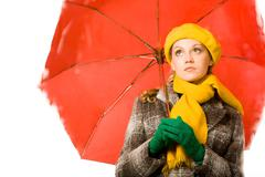 Portrait of sad woman in coat and beret under umbrella during rain Stock Photos