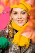 Happy woman in coat and beret looking at camera Stock Photos