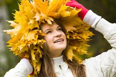 portrait of smiling young woman touching wreath of maple leaves - stock photo