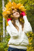 portrait of smiling young woman wearing wreath of maple leaves - stock photo