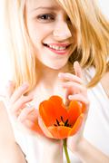 close-up of pretty female holding red beautiful flower in hands and smiling - stock photo