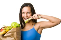 Portrait of pretty girl holding paper sack with fruits and vegetables and eating Stock Photos
