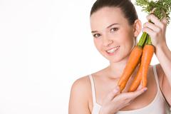 portrait of pretty girl with ripe carrots smiling at camera over white backgroun - stock photo