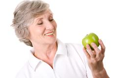 portrait of aged female with green apple ready to eat it - stock photo
