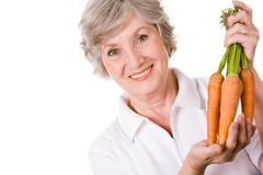 Portrait of elderly woman with ripe carrots smiling at camera over white backgro Stock Photos