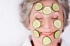 Face of mature woman with cucumber slices on it Stock Photos