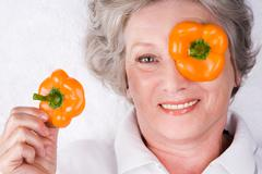 Face of mature woman with taking pepper slice off her eye Stock Photos
